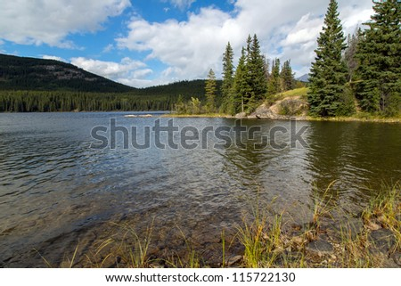 Clear pristine lake surrounded by pine forest with bright sky - stock photo