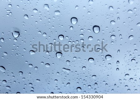 Clear raindrops on a car windscreen against a cloudy blue  sky in early spring  would be ideal for an abstract wallpaper design. - stock photo