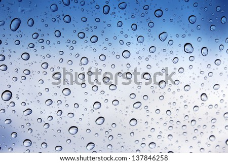 Clear raindrops on windscreen with blue cloudy sky background  ideal for  unique abstract wallpapers. - stock photo