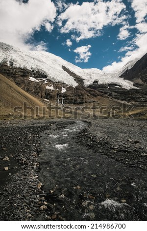 Clear river with rocks leads towards mountains - stock photo
