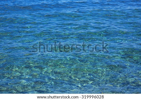 Clear Sea Water with stones and flares. Water ocean background. Clear blue ripple aqua texture  - stock photo