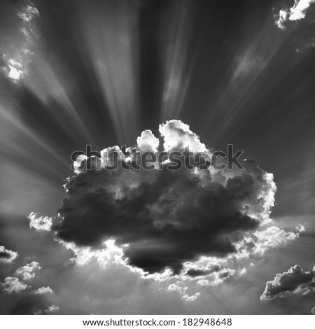Clear skies, sun hidden behind a cloud. You can see the crown of sun rays coming out of the cloud in the sky. - stock photo