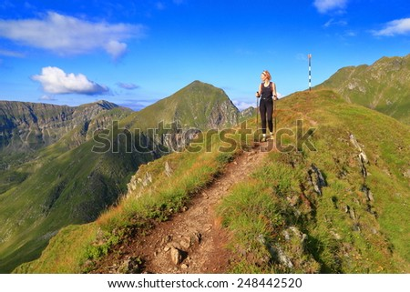 Clear sky above sunny mountains and woman hiker in the morning  - stock photo