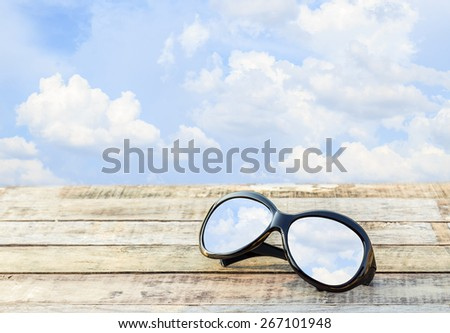 Clear sky in eyeglasses on the wooden table over blue sky background - stock photo