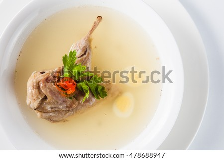 Clear soup quail egg in a white round plate on a light background (top wiev)