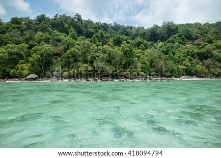 Clear tropical waters of Ko Surin island surrounded by lush green forest, Thailand