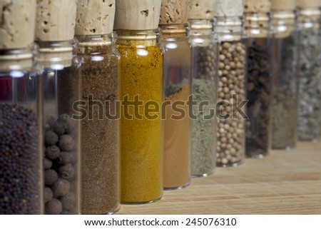 Clear vials filled with various spices lined up on a cutter board. - stock photo