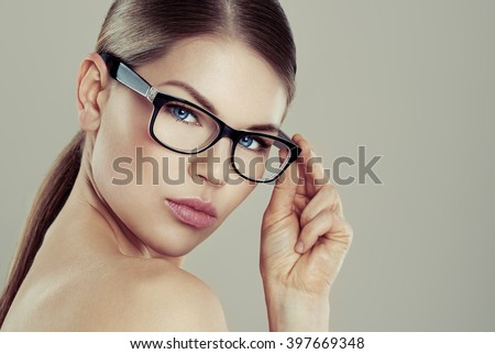 Clear vision concept. Beauty studio portrait of young pretty female wearing stylish eyeglasses with blank space.  - stock photo