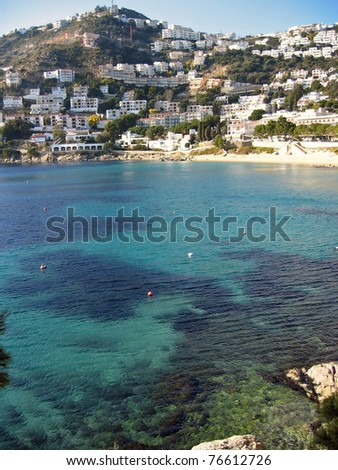 Clear water of the Mediterranean sea in Cala Canyelles Petites with vacation rental  in background, Rosas, Costa Brava, Catalonia, Spain