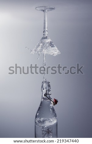 Clear water pour out of bottle splash into a glass with grey back lighting upside down - stock photo