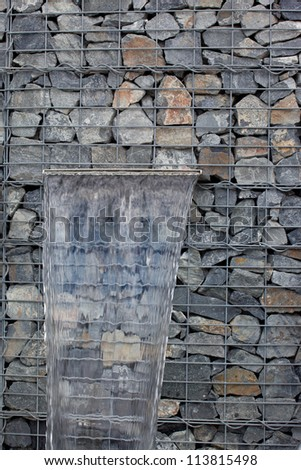 Clear water spring in gabion wall - stock photo