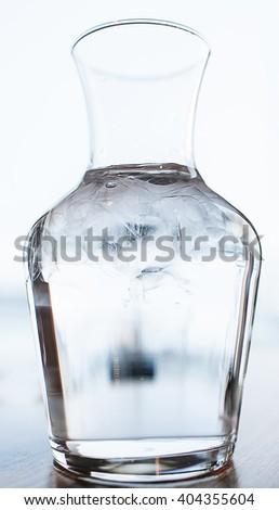 Clear water with ice in a transparent decanter - stock photo