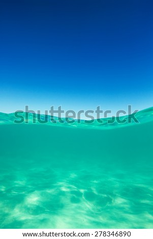 Clear waterline caribbean sea underwater and over with blue sky horizon - stock photo