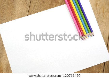 Clear white paper with colorful pencils on the wooden table - stock photo