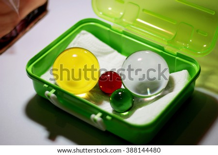 Clearly marbles in a green box. Yellow, red green crystal clear. Color sphere crystal. - stock photo