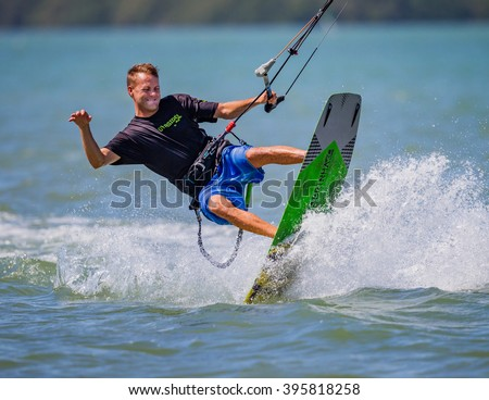 Clearwater, FL- March 12- Happy kite surfer swings his body in the air doing tricks aon March 12, 2016 - stock photo