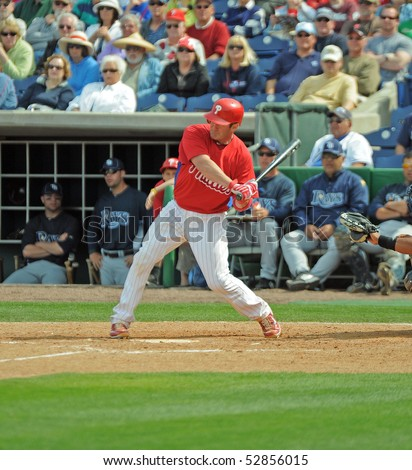 CLEARWATER, FL - MARCH 23: Philadelphia Phillies catcher Brian Schneider swings at a pitch late in a spring training game on March 23, 2010 in Clearwater, FL. - stock photo
