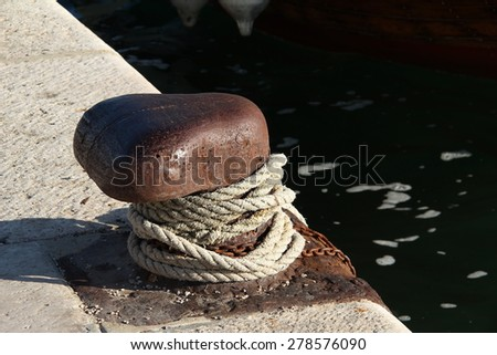 Cleat and rope at sea / Port detail - quayside old metal cleat - bollard with ships mooring rope attached near the Adriatic sea (Croatia-Dalmatia). - stock photo