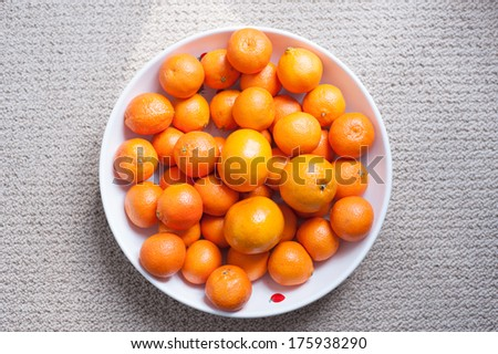 Clementines and tangerines in large white bowl - stock photo