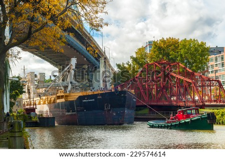 CLEVELAND - OCTOBER 11, 2014: A tugboat guides the lake freighter St. Mary's Cement II, a cement carrier, under a high bridge on the Cuyahoga River on its way to Lake Erie and ports beyond. - stock photo