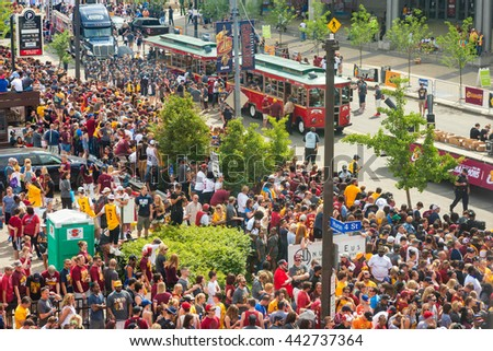 CLEVELAND, OH - JUNE 22, 2016: Unprecedented crowds jam the streets at the start of the Cleveland Cavaliers' NBA championship parade, with participants on board Lolly the Trolley and on the sidewalk. - stock photo