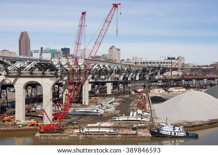 CLEVELAND, OH - MARCH 12: A tugboat on the Cuyahoga River positions a barge with a crane used in the construction of the second span of a new innerbelt bridge in Cleveland, Ohio on March 12, 2016
