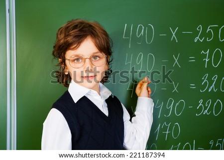 Clever boy holds chalk near blackboard - stock photo