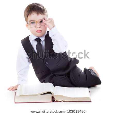 clever boy with a book and wearing glasses isolated in studio - stock photo