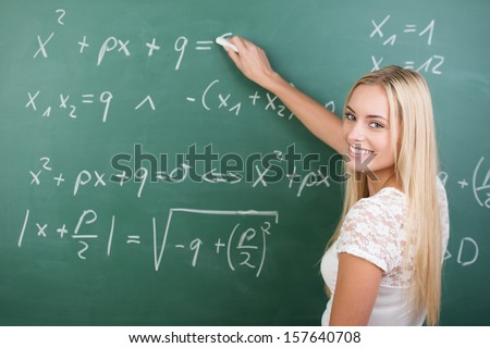 Clever confident female student in the classroom writing on a chalkboard completing mathematical equations - stock photo