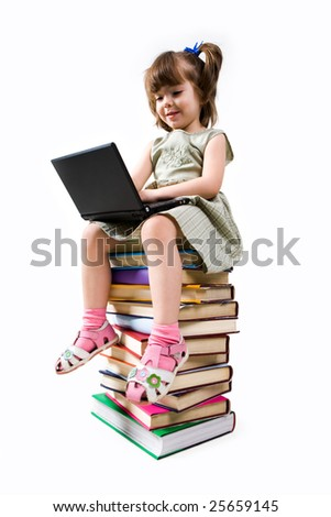 Clever elementary class child sitting on pile of textbooks and typing on laptop