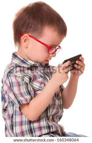 Clever kid is playing with black smart cell phone isolated on white background - stock photo