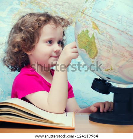 Clever little girl looks at the globe - stock photo