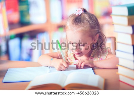 Clever little schoolgirl in glasses at table with books trying to learn new skills