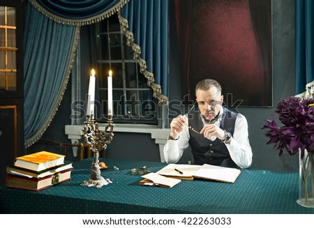 Clever man with eyeglasses in hands at the table in his study