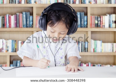 Clever primary school student wearing headset in the library while studying and write on the paper - stock photo
