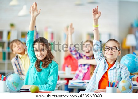 Clever pupils raising hands during lesson - stock photo