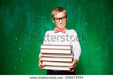 Clever schoolboy with stack of books - stock photo