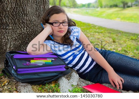 Clever student teenager girl with school bag resting relaxed under park tree - stock photo