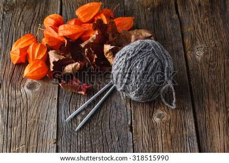 Clew of gray homemade wool yarn with needle. Rustic wooden background - stock photo