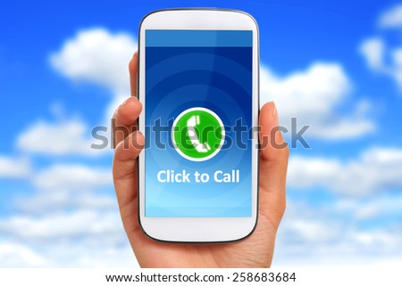 Click to call concept. Hand with phone over blue sky background. - stock photo