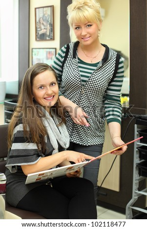 Client and hairdresser with catalog of hair colors look at camera in beauty salon; focus on woman on left