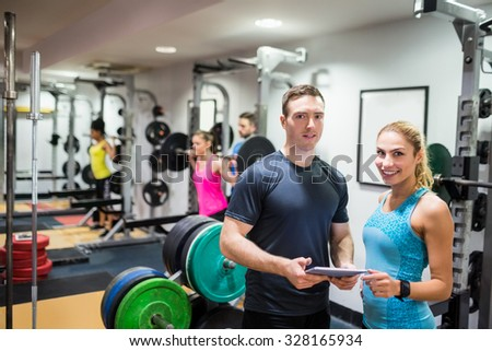 Client and trainer looking at tablet pc at the gym
