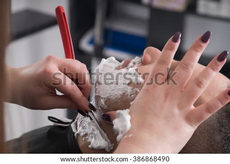Client during beard shaving in barber shop - stock photo