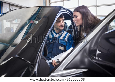 client gets explanaition from the car mechanic over the serviced items of her car. The mechanic sits in the car and points to the dashboard. - stock photo