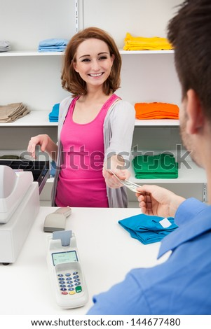 Client Handing Over Credit Card To A Happy Female Cashier - stock photo