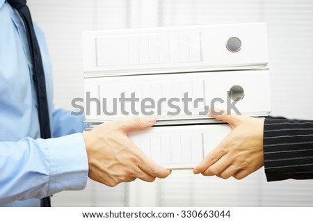 Client is passing documentation in binders to his partner - stock photo