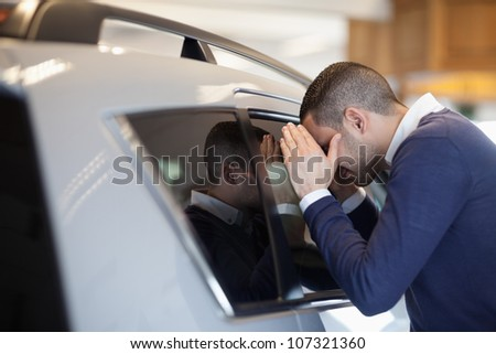 Client looking inside a car in a garage - stock photo