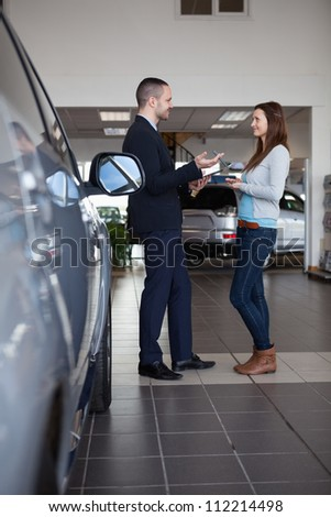 Client speaking with a salesman in a dealership - stock photo
