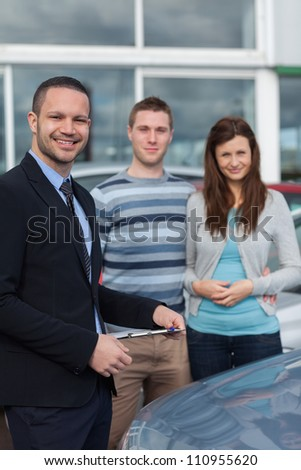 Clients having a meeting with a salesman in a dealership