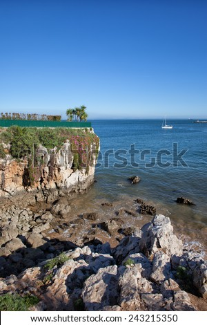 Cliff and rocky shore of the Atlantic Ocean in Cascais, Portugal. - stock photo